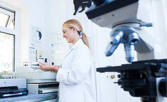 Female veterinarian with blonde hair in the Animal General Cranberry Township lab with microscope